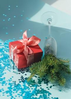 Elegante composizione festiva con una confezione regalo rossa con fiocco in corallo satinato, rami di albero di natale e coriandoli blu cosparsi.