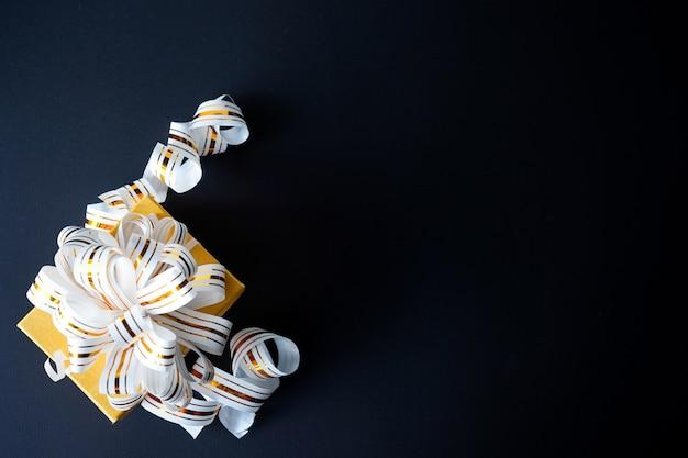 Elegante confezione regalo avvolto in nastro a strisce bianche e oro su sfondo nero con texture.