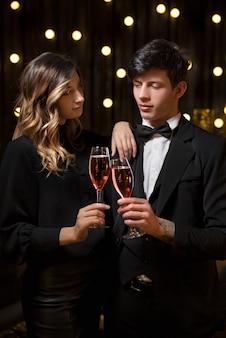 Elegante coppia brindando al nuovo anno con champagne e gioia mentre tintinnano i bicchieri contro le luci scintillanti della festa