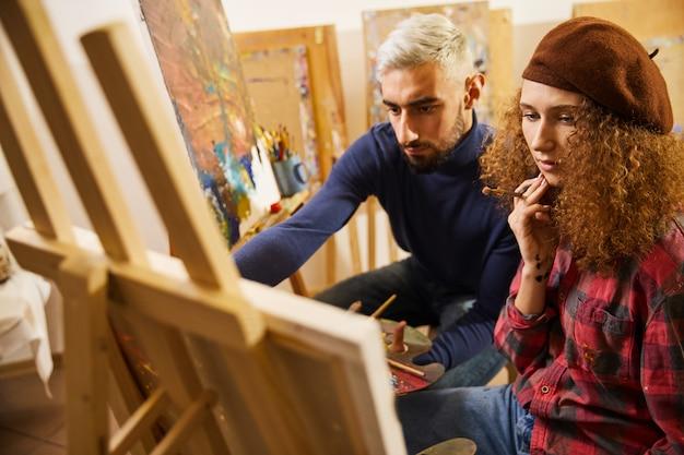 Elegante coppia di artisti disegna un dipinto