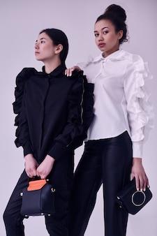 Elegante coppia di donne nere e asiatiche in abiti bianchi e neri alla moda