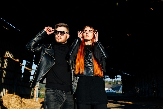 Elegante coppia glamour in giacche di pelle nera in posa in un capannone