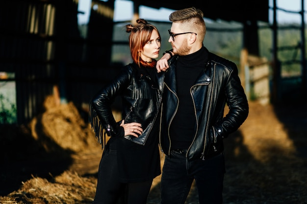 Elegante coppia glamour in giacche di pelle nera in posa in un hangar