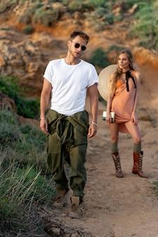 Elegante coppia hipsters un giovane uomo in una maglietta bianca, occhiali e pantaloni larghi, una ragazza in un abito largo, stivali casual e un cappello dietro la schiena. stile boho all'aperto
