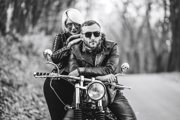 Elegante coppia in bicicletta con una motocicletta rossa