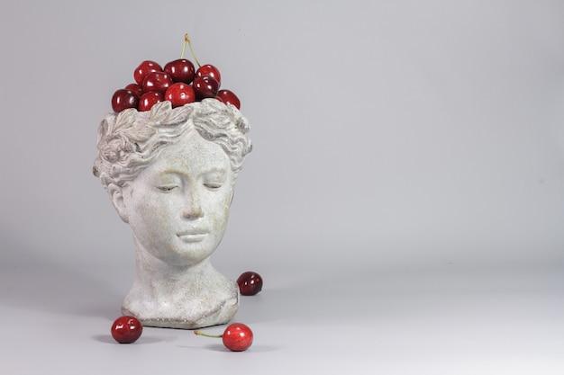Elegante decorazione realizzata a forma di testa di dea greca piena di ciliegie rosse mature. sfondo grigio.