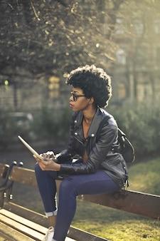 Elegante donna afro in un parco con un tablet