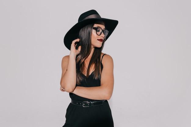 Elegante donna attraente in abito nero con occhiali con rossetto di vite in posa sopra il muro grigio.