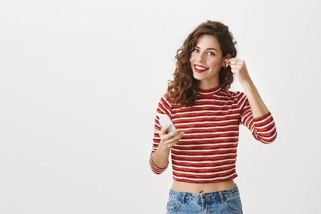 Elegante donna attraente messo su auricolari wireless, tenendo lo smartphone