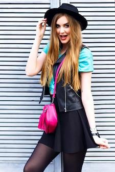 Elegante donna bionda in posa per strada, indossa un abito luminoso hipster, giocose emozioni fresche, divertimento, divertimento, felice vacanza da solo, cappello vintage e minigonna.