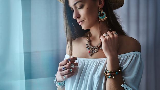Elegante donna boho chic bruna indossa camicetta bianca e cappello di paglia con grandi orecchini, bracciali, collana d'oro e anelli d'argento. vestito bohemien zingaro alla moda hippie con dettagli di gioielli