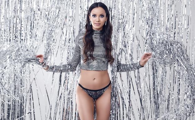 Elegante donna bruna con un corpo perfetto in lussuoso top con paillettes