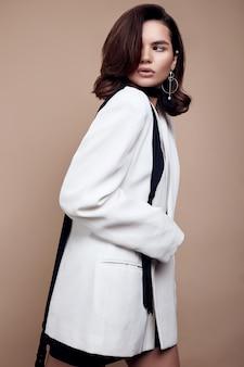 Elegante donna caucasica con i capelli scuri in abito bianco di moda