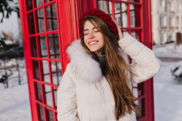Elegante donna dai capelli castani in posa con un sorriso romantico e gli occhi chiusi durante l'inverno in inghilterra. ritratto all'aperto di donna sorridente sognante in berretto di lana rosso che gode del servizio fotografico vicino alla cabina telefonica.