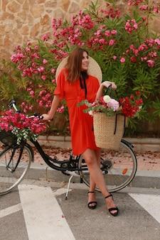 Elegante donna in abito con la bicicletta con cesto di vimini pieno di fiori