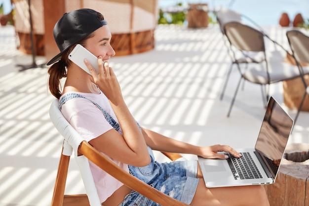 Elegante donna in berretto nero, maglietta bianca casual, messaggi in chat online sul computer portatile, colloqui con il migliore amico su smart phone