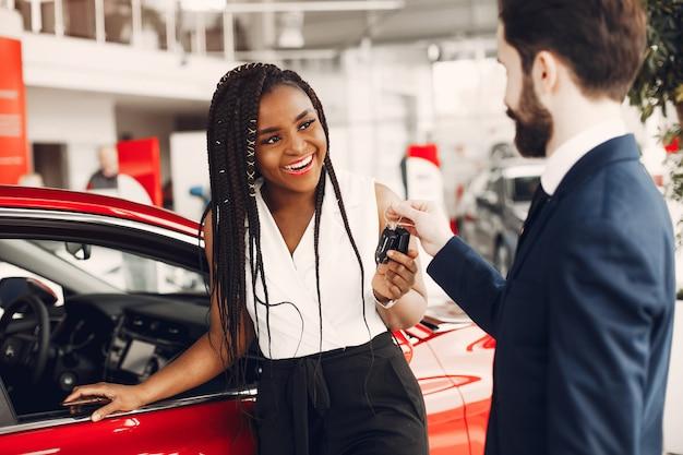 Elegante donna nera in un salone di auto