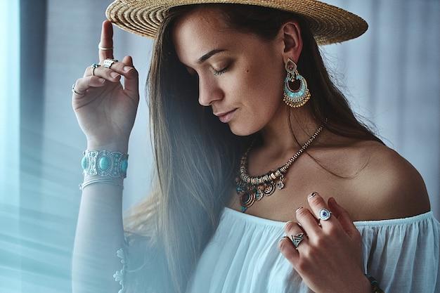 Elegante donna sensuale boho bruna indossa camicetta bianca e cappello di paglia con grandi orecchini, bracciali, collana d'oro e anelli d'argento. vestito bohemien zingaro alla moda hippie con dettagli di gioielli