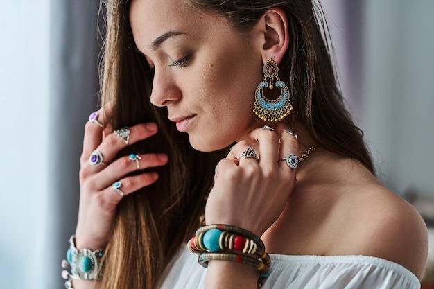 Elegante donna sensuale boho chic in camicetta bianca indossa grandi orecchini, bracciali e anelli d'argento. vestito bohemien zingaro hippie indiano alla moda con dettagli di gioielli imitazione