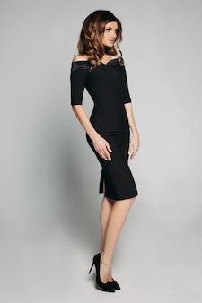 Elegante donna sottile in abito classico nero e tacchi.