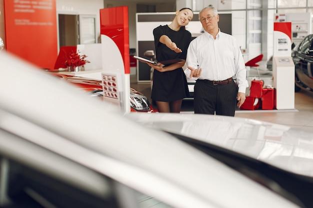 Elegante ed elegante vecchio in un salone di auto