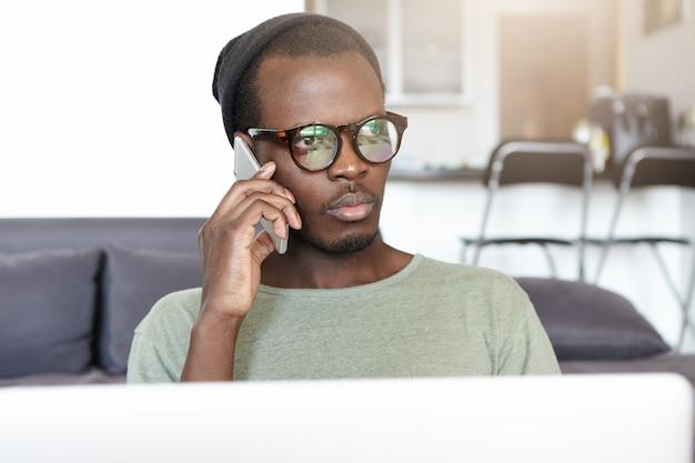 Elegante giovane afroamericano con gli occhiali e cappello seduto sul divano nella hall dell'hotel con il computer portatile e avendo una conversazione seria sul cellulare. persone, stile di vita e tecnologia