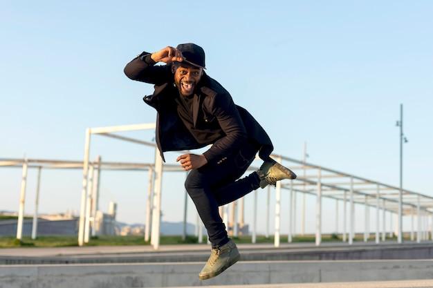 Elegante giovane ballerino maschio in abiti neri alla moda ballare su una strada della città in un pomeriggio d'autunno