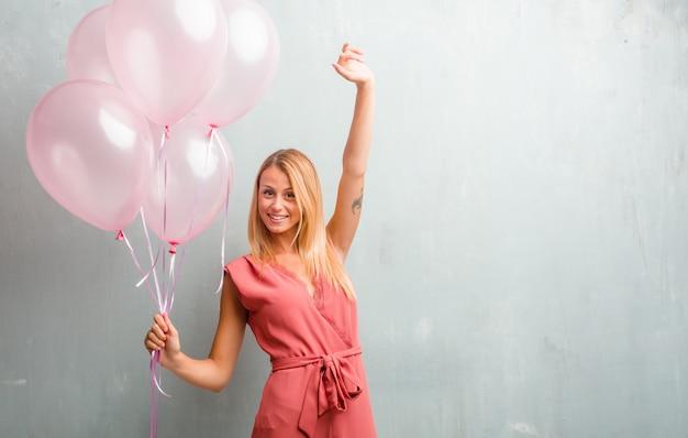 Elegante giovane donna bionda che tiene palloncini rosa contro un muro.