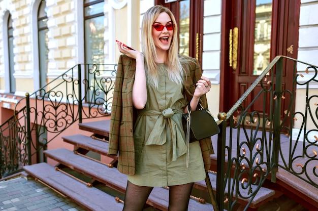 Elegante giovane donna bionda di affari che parla dal suo telefono e posa per strada a parigi, vestito elegante femminile alla moda grange, giacca oversize, colori caldi.
