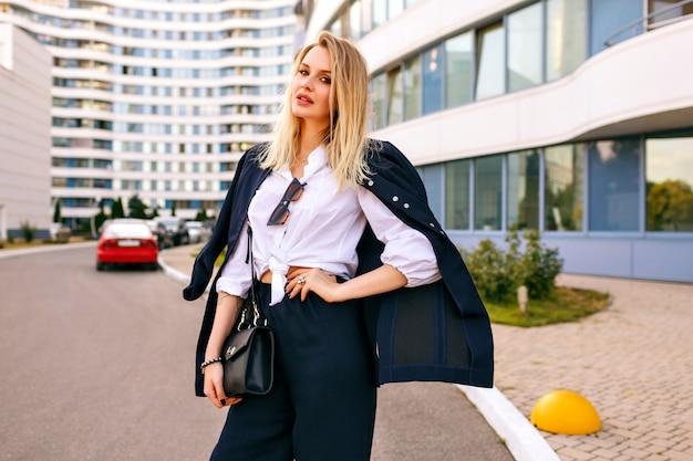 Elegante giovane donna che indossa un abito blu scuro alla moda, in posa vicino a edifici moderni, accessori alla moda, sorridendo e godendo di una soleggiata giornata estiva gratuita, camminando vicino all'ufficio.