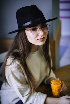 Elegante giovane donna in cappello e occhiali da vista con un bicchiere di bevanda