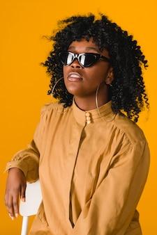 Elegante giovane donna nera che indossa occhiali da sole e orecchini a cerchio