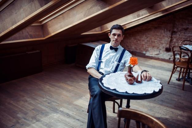 Elegante giovane in bretelle e bicchieri nella caffetteria