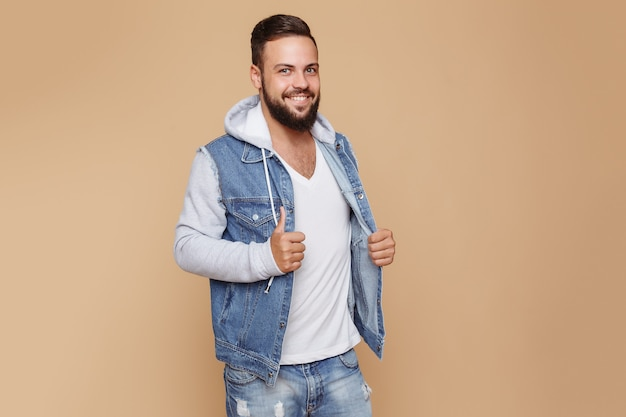 Elegante giovane ragazzo allegro con una bella barba in una giacca di jeans e t-shirt bianca su uno spazio semplice color crema. concetto di pubblicità giacca di jeans per tabellone per le affissioni.
