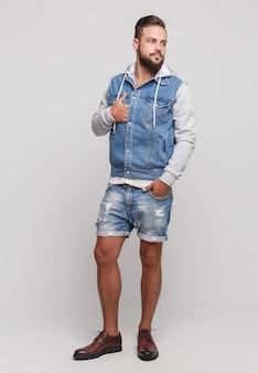 Elegante giovane ragazzo allegro con una bella barba in una giacca di jeans, una maglietta bianca e pantaloncini di jeans su un semplice spazio grigio. giacca di jeans e pantaloncini di jeans concetto di pubblicità per cartelloni pubblicitari.