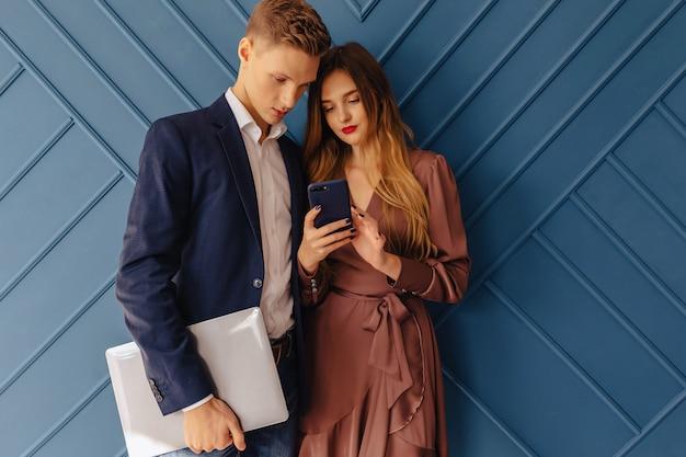 Elegante giovane ragazzo con laptop e ragazza con telefono insieme, giovane uomo d'affari
