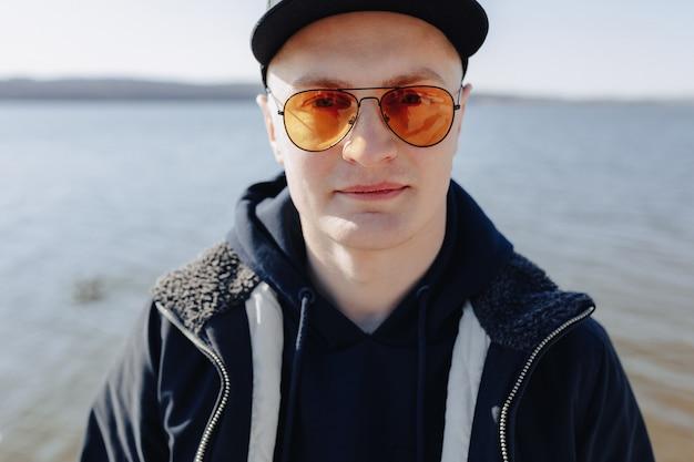 Elegante giovane ragazzo in occhiali arancioni, giacca e berretto, camminare intorno al lago