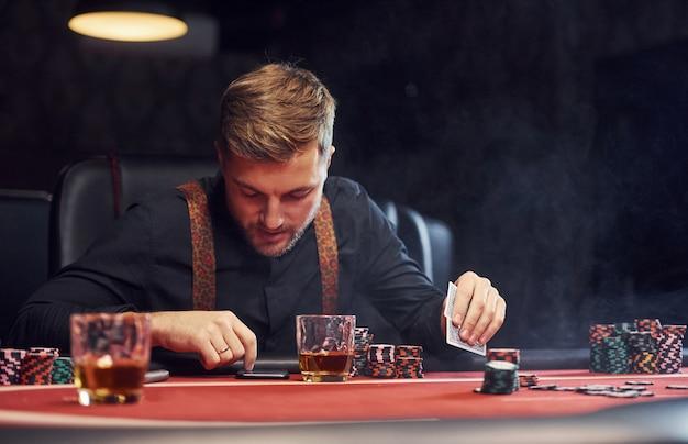 Elegante giovane si siede nel casinò, utilizzando il telefono e gioca a poker