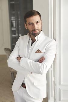 Elegante giovane uomo bello con la barba in un abito classico bianco. interni dell'hotel.