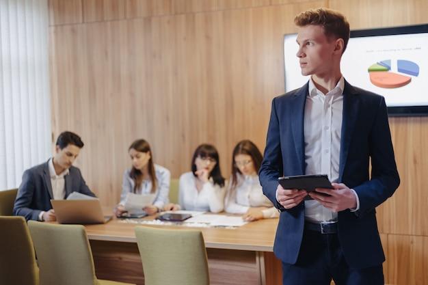 Elegante giovane uomo d'affari che indossa una giacca e una camicia che lavora con un tablet