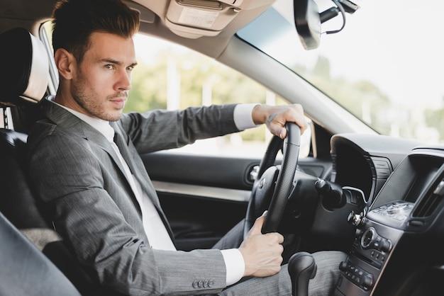 Elegante giovane uomo d'affari guida auto