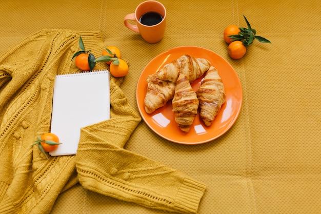 Elegante immagine invernale nei colori arancioni dall'alto di maglione lavorato a maglia, croissant, clementine e taccuino sul tavolo