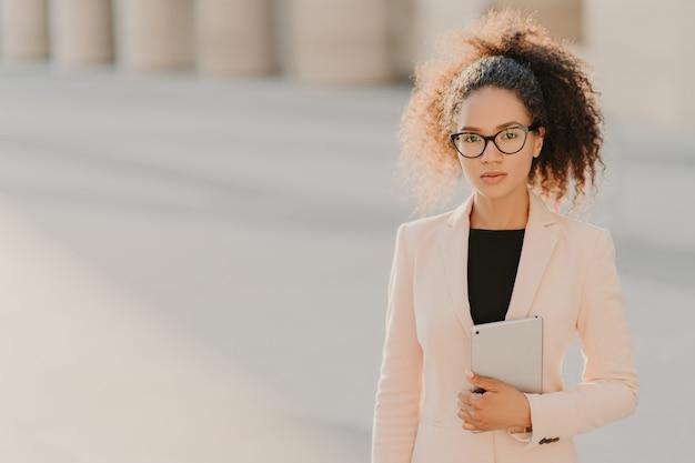 Elegante imprenditrice afroamericana utilizza tablet computer all'aperto, indossa giacca bianca formale