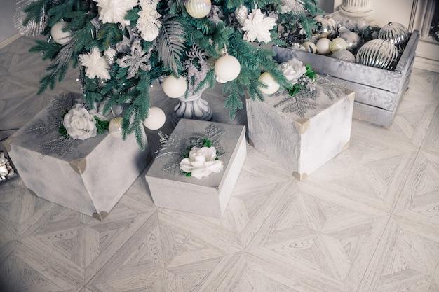 Elegante interno di natale con un elegante divano. casa confortevole presenta regali sotto l'albero nel salotto