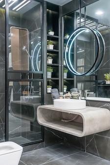 Elegante lavandino bianco in piedi su una mensola grigia. uno specchio rotondo è sospeso sopra di esso.