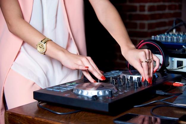 Elegante mani femminili belle dj sul pannello di controllo.
