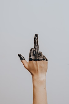 Elegante mano femminile immersa in vernice nera. isolato. gesto.