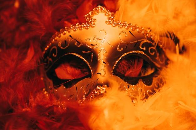 Elegante maschera veneziana di carnevale dorata con piume