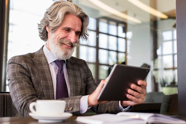 Elegante maschio adulto azienda tablet