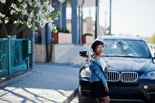 Elegante modello afro-americano in occhiali cappello, giacca di jeans e gonna nera poste all'aperto contro auto suv business nero.